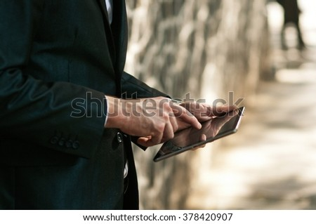 Close up of a businessman working on the digital tablet - stock photo