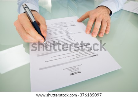Close-up Of A Businessperson With Resume At Desk - stock photo