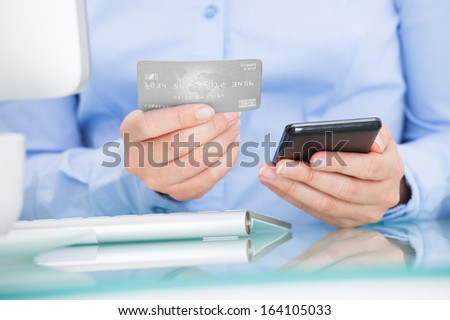 Close-up Of A Businesswoman Holding Cellphone Using Credit Card Shopping Online - stock photo