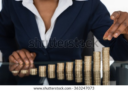 Close-up Of A Businesswoman Making Stack Of Coins - stock photo