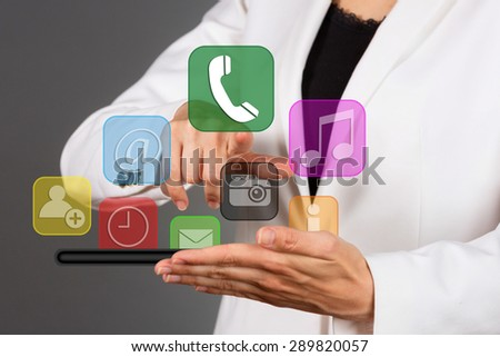 Close up of a businesswoman pressing virtual icons, isolated on dark grey background. - stock photo