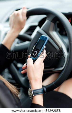 Close-up of a businesswoman sending a text while driving to work - stock photo