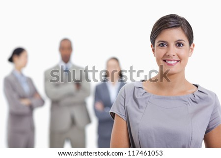 Close-up of a businesswoman smiling and a team crossing their arms in background - stock photo