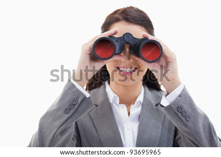 Close-up of a businesswoman smiling and looking through binoculars against white background - stock photo