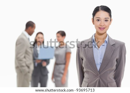 Close-up of a businesswoman with co-workers watching a laptop in the background - stock photo