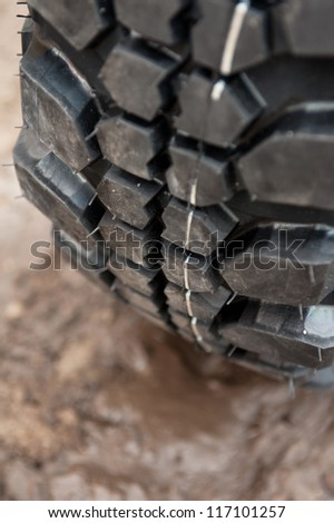 Close up of a car tire on a dirty road. - stock photo