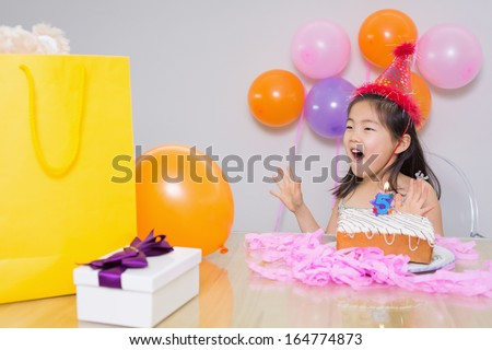 Close-up of a cheerful surprised little girl at her birthday party - stock photo