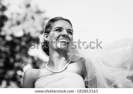 Close-up of a cheerful young beautiful bride in the park - stock photo