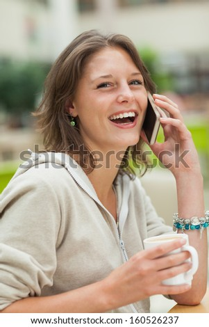 Close-up of a cheerful young woman using mobile phone while drinking coffee - stock photo
