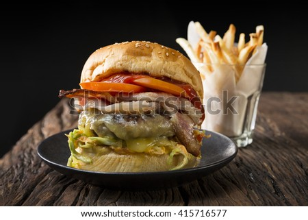 Close Up of a cheese burger with fresh toppings on bread bun. Gourmet burger with fries on a rustic wooden table and dark background. - stock photo