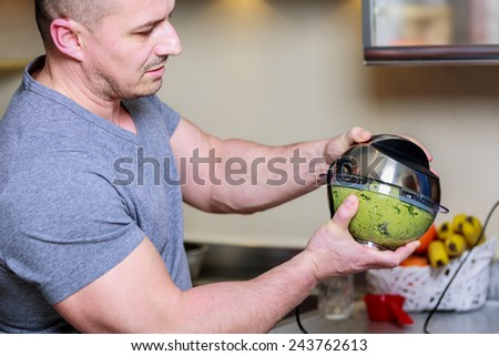 Close-up of a chef using a hand blender to make pesto - stock photo