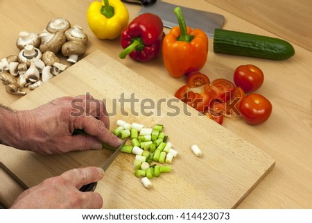 Close up of a chefs hands cutting some salad onions on a wooden chopping board aside a selection of mixed vegetables - stock photo