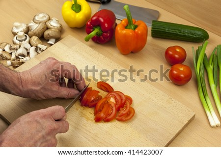 Close up of a chefs hands slicing a salad tomato on a wooden chopping board aside a selection of cut mixed vegetables - stock photo