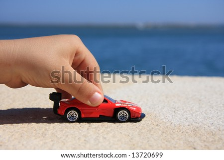 Close-up of a child hand playing with a red car - stock photo
