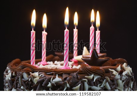 Close up of a chocolate cake with lighted candles - stock photo