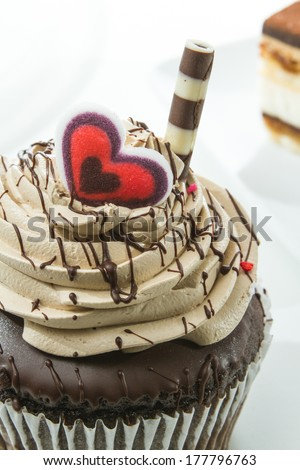 close up of a chocolate cupcake with cream frosting, and a sugar heart garnish isolated on a white background - stock photo
