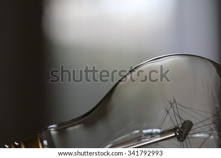 Close-up of a clear bulb with blurry white and grey background. - stock photo