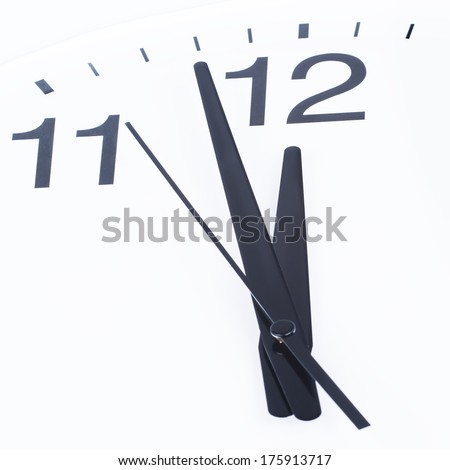 Close up of a clock face showing the hands at two minutes to midday - stock photo