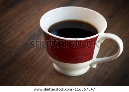 Close up of a coffee mug on a dark wooden table. - stock photo
