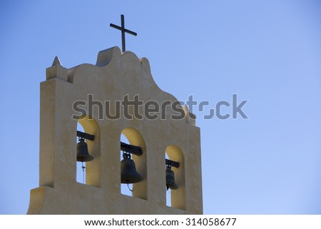 Close up of a colonial church with tree bells and a cross against a clear blue sky in Cachi small town within Calchaqui Valleys in Salta Province. Argentina - stock photo