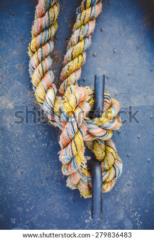 Close-up of a color mooring rope tied around a cleat. - stock photo