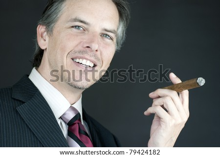 Close-up of a confident businessman holding a lit cigar. - stock photo