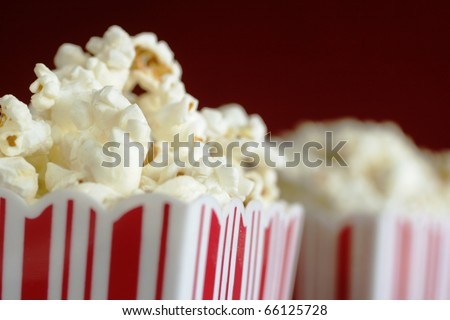 Close up of a container full of pop corn with a second one in background - stock photo
