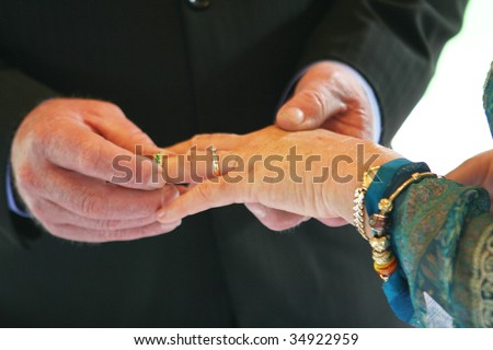 Close-up of a couple exchanging wedding rings during a ceremony. - stock photo