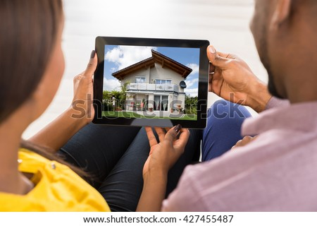 Close-up Of A Couple Looking At House On Digital Tablet - stock photo