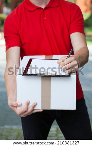 Close-up of a courier writing a transport document - stock photo