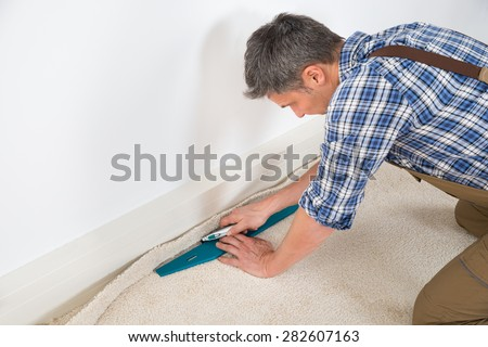 Close-up Of A Craftsman Fitting Carpet On Floor - stock photo