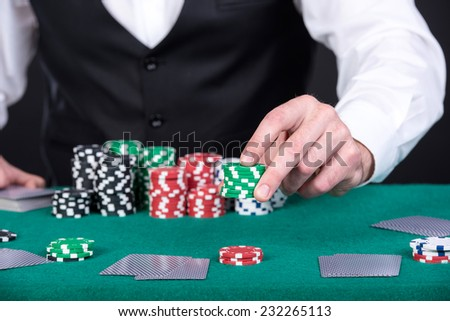Close-up of a croupier is holding gambling chips on table. - stock photo