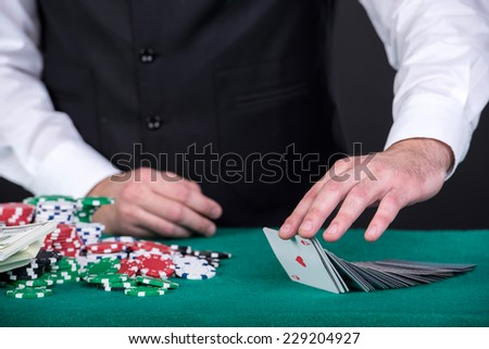 Close-up of a croupiers hand with  gambling cards and chips on the table. - stock photo