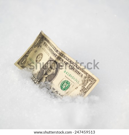 Close up of a crumpled dollar bill in a snow, lost and found  concept - stock photo