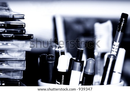 Close-up of a cup of pens/markers and a stack of computer disks on an office desk (Dark blue effect). - stock photo