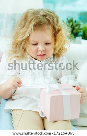 Close-up of a cute girl unwrapping her birthday present - stock photo