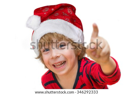 Close-up of a cute little boy with Santa, red shirt, smiling happily and pointing isolated on white background  - stock photo
