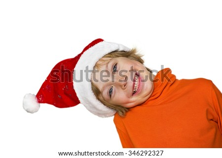 Close-up of a cute little boy with Santa, smiling, head sideways,  looking around the corner isolated on white background  - stock photo