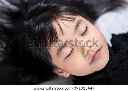 Close-up of a cute little girl sleeping. - stock photo