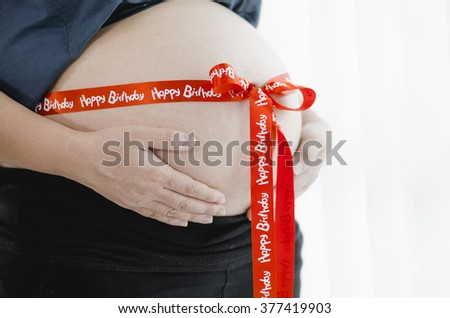Close up of a cute pregnant Happy birth day in home - stock photo
