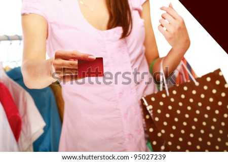 Close-up of a cute woman paying with her credit card in a shop - stock photo