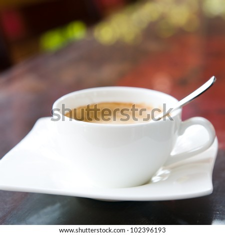close up of  a delicious cup of coffee on wooden table. - stock photo