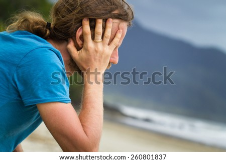 Close-up of a depression, lonely man at the beach - stock photo