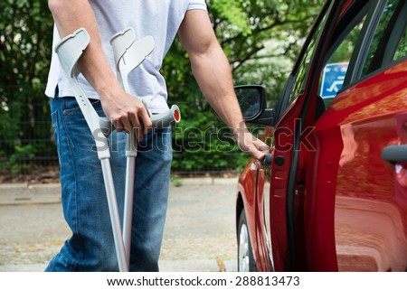 Close-up Of A Disabled Man With Crutches Opening Door Of A Car - stock photo