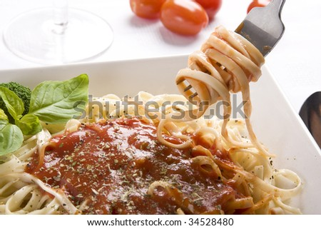 Close up of a dish of pasta and fork lifting some of it. Focus at the middle and at the fork. - stock photo