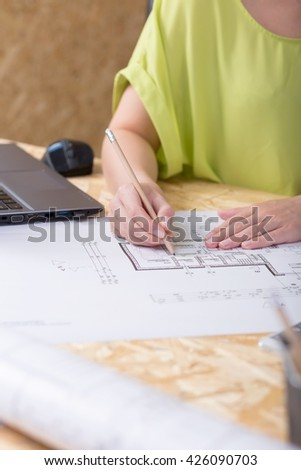 Close-up of a drawing table in an architect's office with a young woman making some corrections on a technical drawing - stock photo