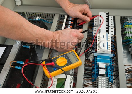 Close-up Of A Electrician Checking Fuse Box With Multimeter - stock photo