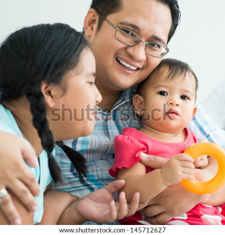 Close-up of a father with a child looking at camera on the foreground - stock photo