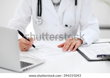 Close-up of a female doctor filling  out application form , sitting at the table in the hospital - stock photo