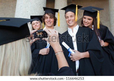 Close-up of a female graduate taking a picture of her friend in front of the university - stock photo